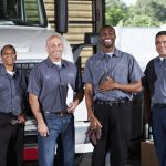 Multi-ehnic workers in employee uniforms at a service garage at trucking company.