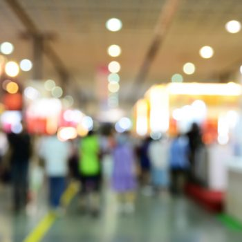Blurred image of people walking in a field service expo
