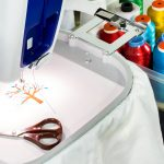 The emboridery machine and accessories are color thread, cutter, scissors, tool box and hoop making a branded apparel shirt with company logo.